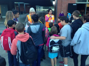 Students at Thomas Edison Language Institute receive stickers and backpack reflectors.