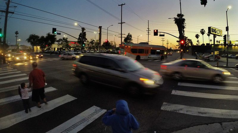 Pedestrians cross at the intersection of Slauson and Western Avenues in Los Angeles on April 14, 2015. (Gina Ferazzi / Los Angeles Times).
